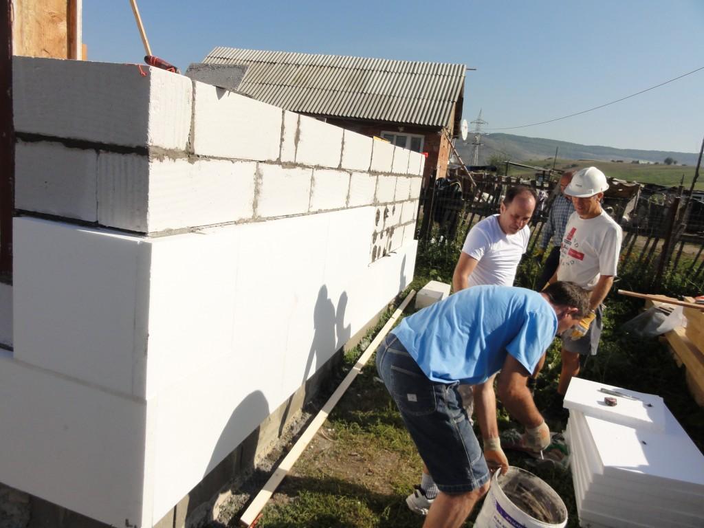 Simon and Silviu applying polystyrene insulation