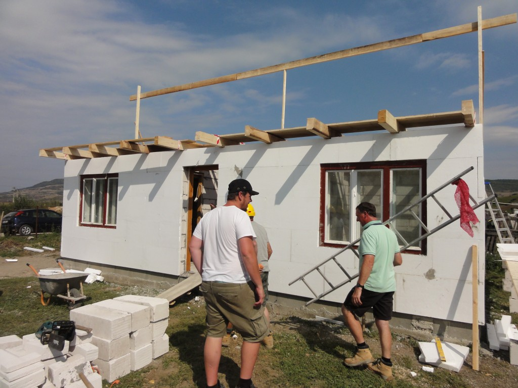 The roof structure starts to go up on the larger house