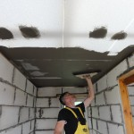 One of the Romanian volunteers finishes the ceiling in the smaller house