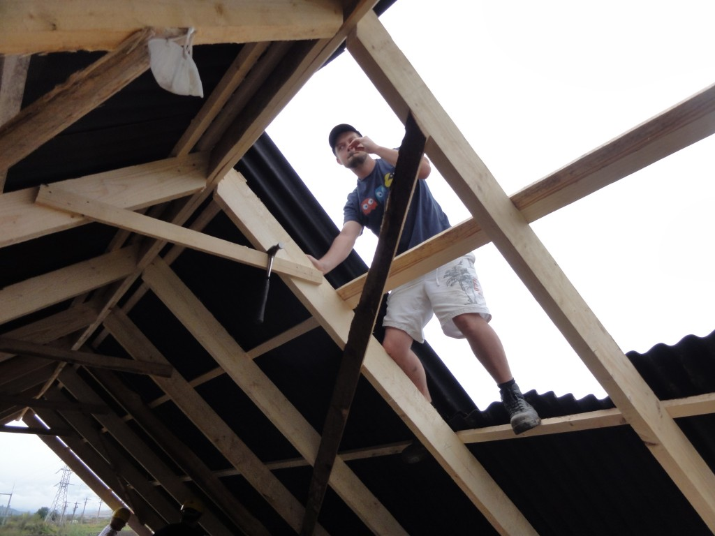Sam working on the roof of the larger house